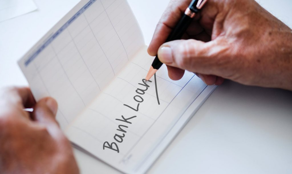 person writing bank loan on paper