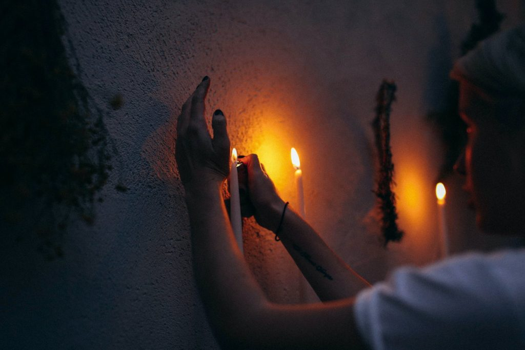 crop woman lighting candle in dark room
